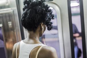 Back view of woman with earphones  in underground trainの写真素材 [FYI04343253]