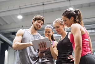 Group of happy athletes with tablet after exercising in gymの写真素材 [FYI04343269]