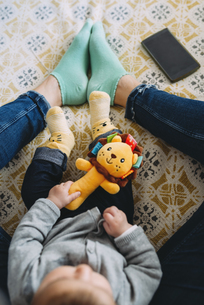 Mother playing with her baby daughter on couchの写真素材 [FYI04343271]