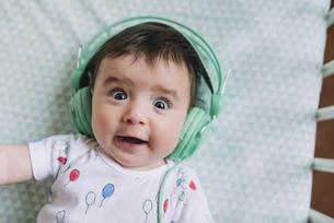 Portrait of baby girl with headphones lying in cribの写真素材 [FYI04343276]