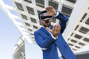 Young businessman wearing VR glasses outdoorsの写真素材 [FYI04343279]