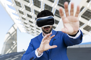 Young businessman wearing VR glasses outdoorsの写真素材 [FYI04343284]