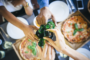 Group of friends having pizza and beer at homeの写真素材 [FYI04343292]