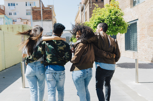 Rear view of stylish friends walking on urban streetの写真素材 [FYI04343355]