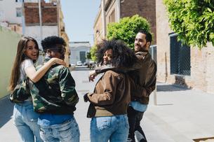 Happy stylish friends walking on urban streetの写真素材 [FYI04343356]