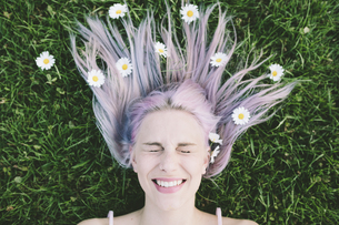 Portrait of woman lying on grass with eyes closed and daisieの写真素材 [FYI04343359]