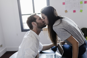 Happy couple with laptop at home kissingの写真素材 [FYI04343361]