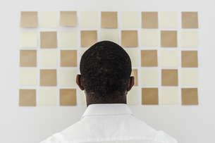 Man looking at adhesive notes on wall in officeの写真素材 [FYI04343374]