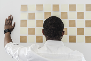 Man looking at adhesive notes on wall in officeの写真素材 [FYI04343375]