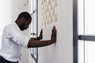 Man leaning against wall  with adhesive notes in officeの写真素材 [FYI04343376]
