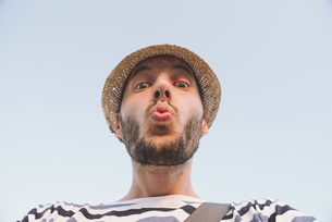 Man with straw hat kissing to the cameraの写真素材 [FYI04343378]
