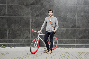Portrait of young man with his racing cycleの写真素材 [FYI04343389]