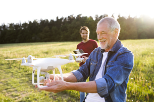 Senior father and his adult son with drone on a meadowの写真素材 [FYI04343400]