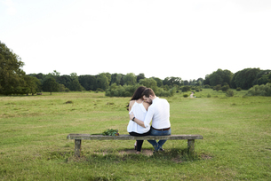 Back view of couple sitting on a bench in a parkの写真素材 [FYI04343416]