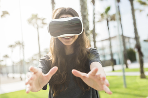 Young woman wearing VR glasses outdoorsの写真素材 [FYI04343417]