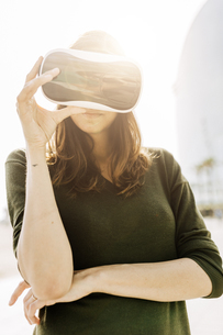 Young woman wearing VR glasses outdoorsの写真素材 [FYI04343429]