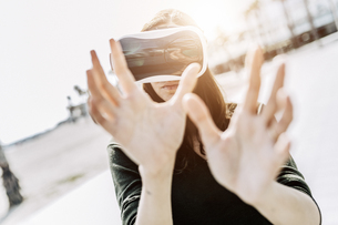 Young woman wearing VR glasses outdoorsの写真素材 [FYI04343430]