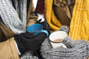 Young couple wearing gloves holding cups of tea in winter, cの写真素材 [FYI04343457]