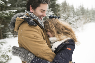 Happy young couple having fun in snow-covered winter forestの写真素材 [FYI04343458]