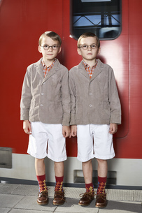 Twin brothers standing in front of commuter lineの写真素材 [FYI04343460]