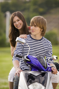 Young couple sitting on moped, smilingの写真素材 [FYI04343483]