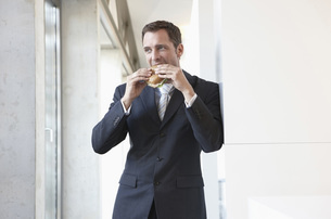 Germany, Cologne, Businessman eating sandwich, portraitの写真素材 [FYI04343537]