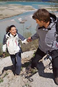 Germany, Bavaria, Couple trekking, man helping womanの写真素材 [FYI04343552]