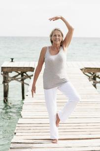 Spain, Senior woman doing yoga on jetty at the seaの写真素材 [FYI04343599]