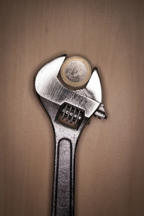 Adjustable spanner with euro coin on wooden backgroundの写真素材 [FYI04343633]