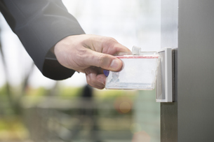 Germany, Hannover, Businessman using access card, close upの写真素材 [FYI04343655]