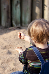 Germany, Kiel, girl plays with sand on playground, from behiの写真素材 [FYI04343685]