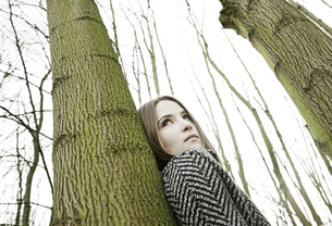 Portrait of teenage girl leaning against tree trunkの写真素材 [FYI04343756]