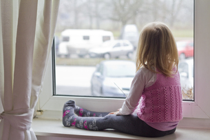 Little girl sitting on window sill looking out of windowの写真素材 [FYI04343780]