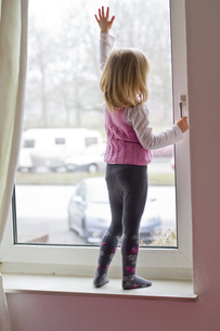 Little girl standing on window sill looking out of windowの写真素材 [FYI04343781]
