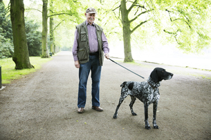Senior man walking with his German Shorthaired Pointer in ciの写真素材 [FYI04343793]