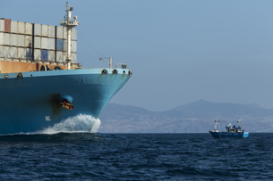 Spain, Andalusia, Tarifa, Container ship and fishing boatの写真素材 [FYI04343813]