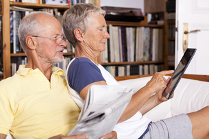 Senior couple sitting on couch with newspaper using digitalの写真素材 [FYI04343821]