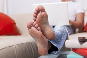 Man sitting barefoot on a couch using laptop at homeの写真素材 [FYI04343822]