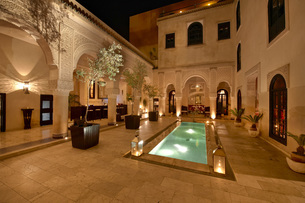 Morocco, Fes, Hotel Riad Fes, courtyard with lightened poolの写真素材 [FYI04343838]