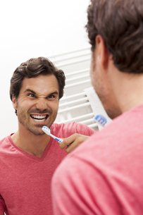 Mirror image of man with toothbrush pouting a mouthの写真素材 [FYI04343857]