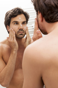 Mirror image of young man applying face creamの写真素材 [FYI04343859]