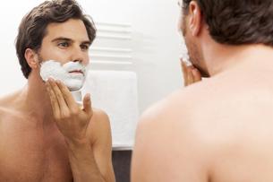 Mirror image of young man applying shaving foamの写真素材 [FYI04343860]