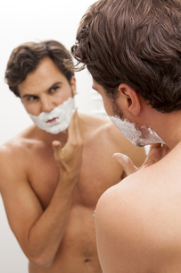 Young man applying shaving foam while looking in the mirrorの写真素材 [FYI04343861]