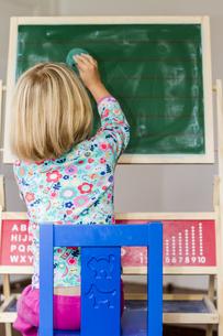Little girl writing on blackboardの写真素材 [FYI04343869]