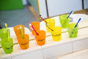 Plastic cups with toothbrushes with manes of kids in nurseryの写真素材 [FYI04343940]