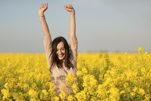 Happy woman in a blossoming rape fieldの写真素材 [FYI04343981]