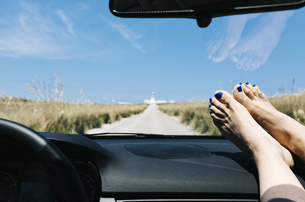 Spain, Menorca, feet on the dashboard, driving on empty roadの写真素材 [FYI04344024]