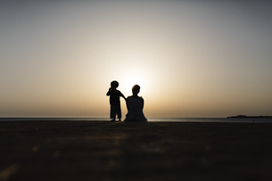 Spain, Menorca, silhouette of mother and son watching the suの写真素材 [FYI04344025]
