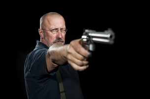 Mature man with revolver aimingの写真素材 [FYI04344036]