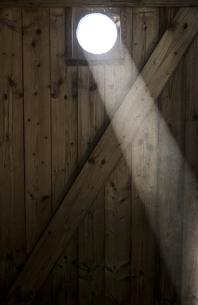Ray falling through oculus of wooden doorの写真素材 [FYI04344079]